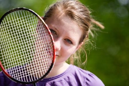 Portrait of teenage girl with badminton racket photo