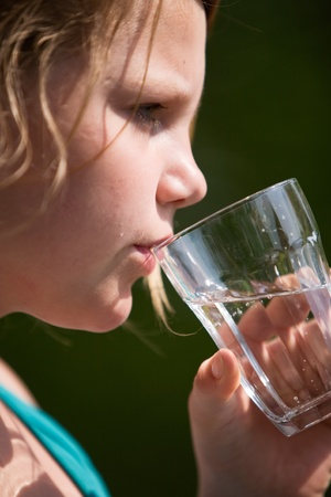 Profile of young girl holding glass of water photo