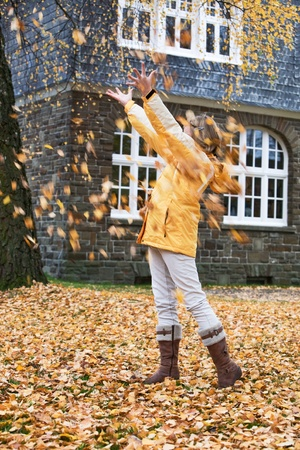 Young girl under falling autumn leaves Stock Photo - 13317551