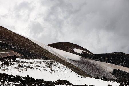 volcano slope: Lava rocks with snow on volcano slope of Etna, Sicily, Italy