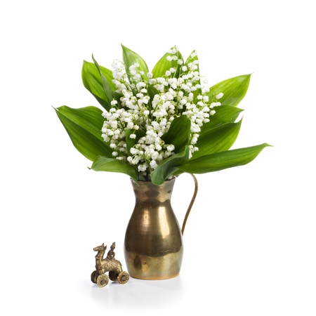 Old cooper jug with Lilly flowers and antique toy on white background photo