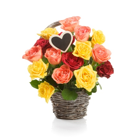Basket with fresh colorful roses and heart on a stick on white photo