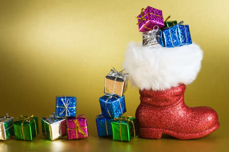 Red Santa boot and gifts on gold background photo