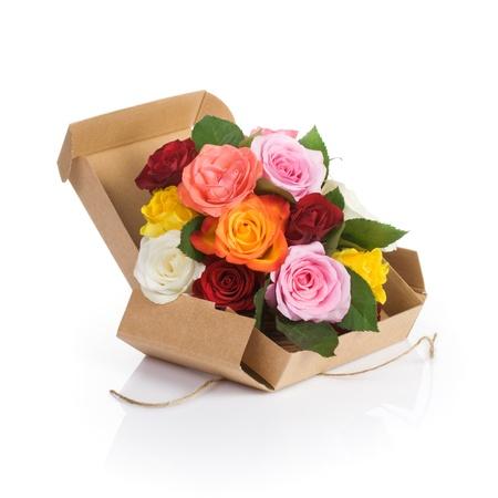 Cardboard box of fresh roses on white background photo