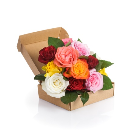 Cardboard box of fresh roses on white background photo