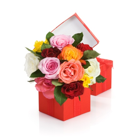 Red gift box with colorful roses on white background Фото со стока
