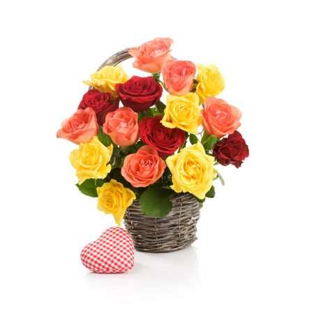 Basket with fresh colorful roses and fabric heart on white background photo
