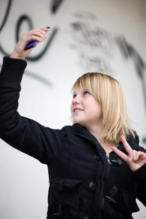 Teenage girl taking self portrait with smart phone photo