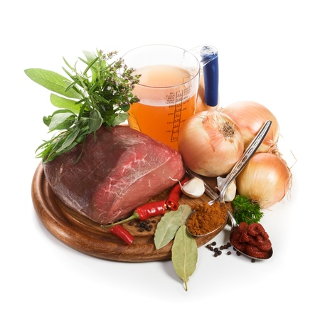 Meat and ingredients for goulash on chopping board, close-up, white background photo