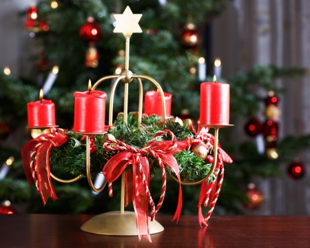Advent wreath with four burning red candles, Christmas tree on background Stock Photo - 15657488