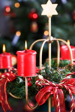 Advent wreath with burning red candles, Christmas tree on background photo