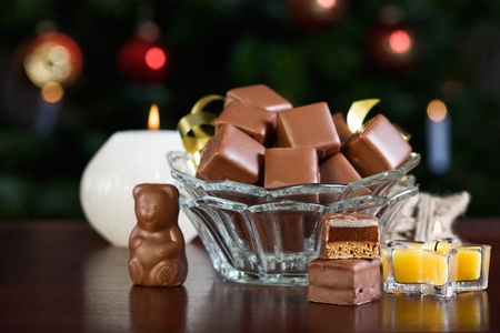 Bowl with Dominosteine, traditional German Advent confectionary, illuminated Christmas tree on background photo