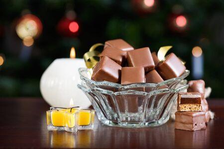 cioccolato natale: Ciotola con Dominosteine, tradizionale pasticceria dell'Avvento tedesco, illuminato albero di Natale su sfondo Archivio Fotografico