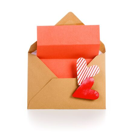Envelope with red notepad and two hearts on white photo