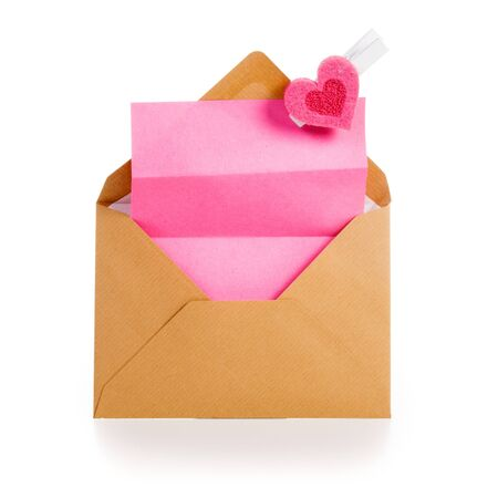 Envelope with pink notepad and heart on white background photo