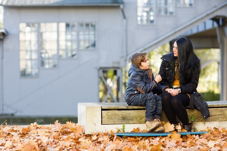 Mother and son sitting on bench and talking in front of abandoned railroad station Standard-Bild