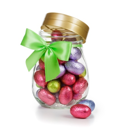 Open glass jar full of chocolate candy Easter eggs wrapped in foil and decorated with bow clipping path included photo