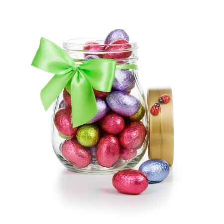 Open glass jar full of chocolate candy Easter eggs wrapped in foil decorated with bow and ladybugs clipping path included Stock Photo - 17077461