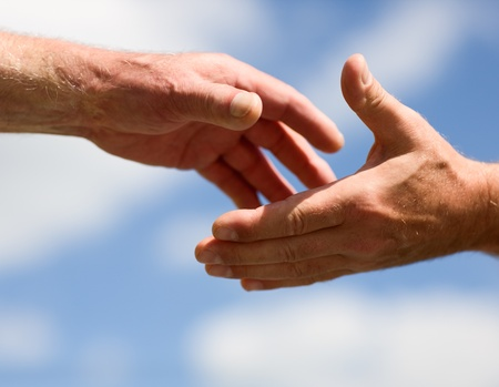 Two hands reaching out to each other against sky