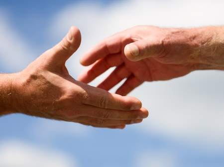 Twee handen reiken naar elkaar tegen de blauwe hemel