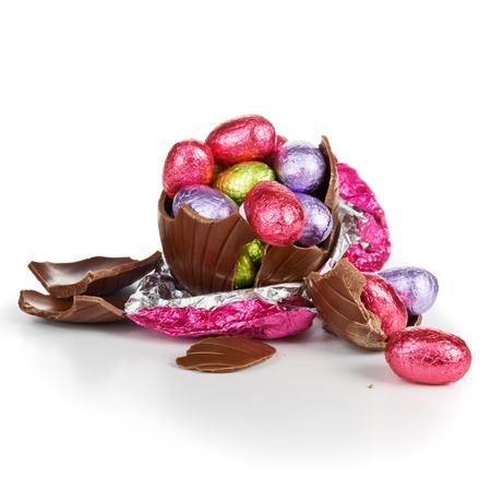 chocolate eggs: Broken chocolate Easter egg wrapped in pink foil with colorful candies on white background