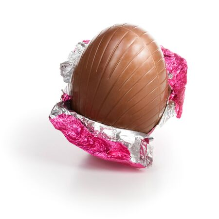 Chocolate candy Easter egg wrapped in pink foil on white background clipping path included