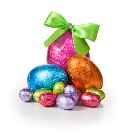 Group of colorful candy Easter eggs wrapped in foil with bow photo