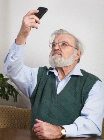 photography themes: Senior man taking self portrait with smart phone