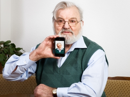 Senior holding smart phone and showing his picture photo