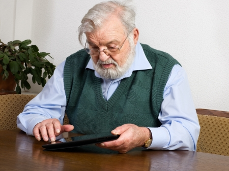 Senior man using his digital tablet photo