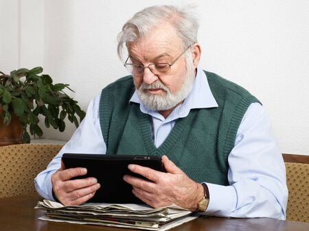 Senior man reading newspaper on digital tablet photo