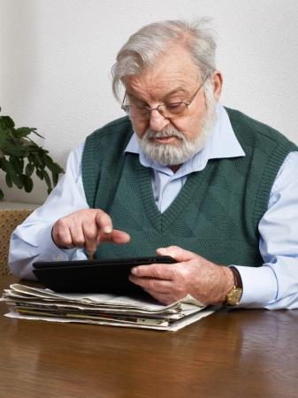 Senior man reading newspaper on digital tablet photo