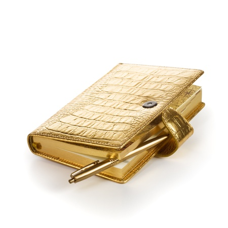 Luxury golden leather notebook with pen on white background photo
