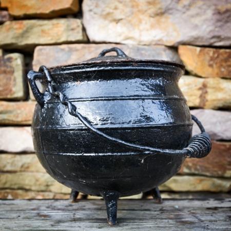 黒ダッチ オーブン、アンティーク クッキング ポット、レンガの壁