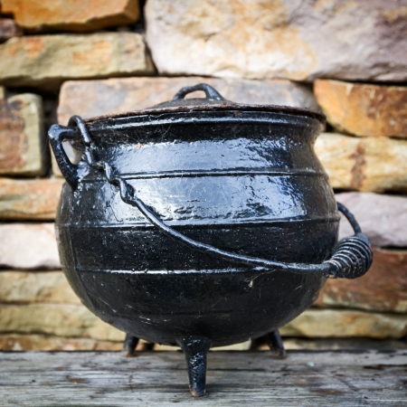 Black dutch oven, antique cooking pot, against brick wall