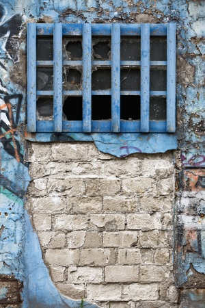 Aged weathered brick wall with graffiti and blue window photo