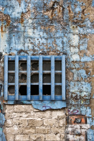 window graffiti: Aged weathered brick wall with graffiti and blue window