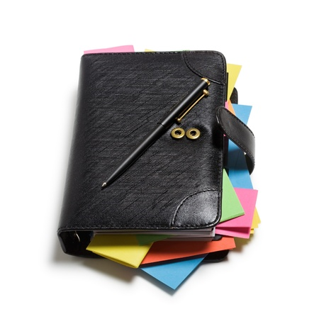 Black notebook with colorful note papers and pen on white background, clipping path included photo