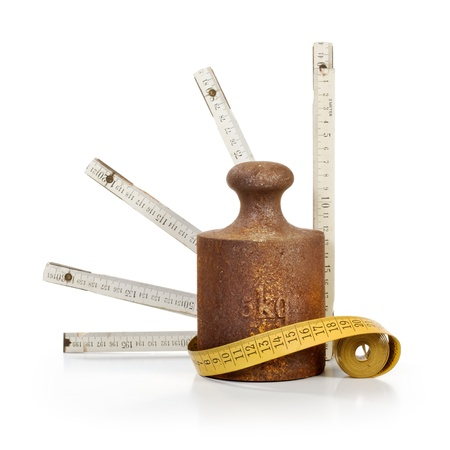 Old rusty weight, tape measure and yardstick on white background   photo