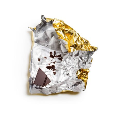 Piece of chocolate bar on wrapper with clipping path photo