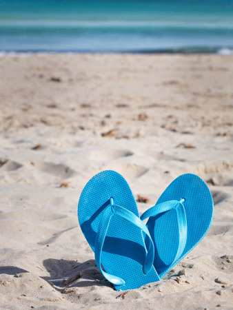 Pair of blue flip flops on sand beach photo