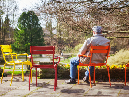 old man sitting: Rear view of elderly man sitting on chair in early spring park Stock Photo