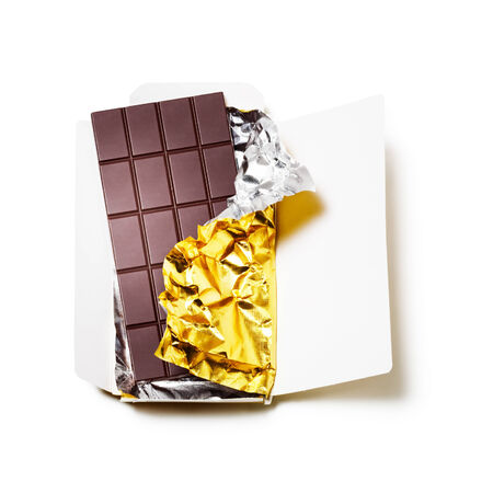 Chocolate bar wrapped in foil with open cardboard on white background photo