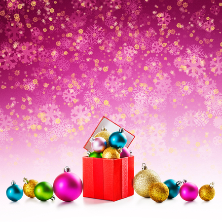 Red gift box with colorful christmas balls on pink snowflakes background  photo