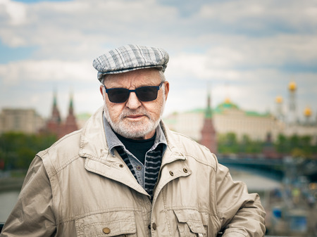 Portrait of old man in sunglasses and cap. Tourist in front of the Kremlin, Moscow. Travel destination. photo