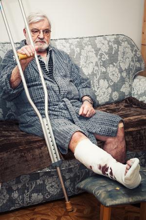 fractura: Hombre mayor con la pierna rota sentado en el sofá en casa, con muletas Foto de archivo