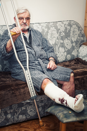 Senior man with broken leg sitting on sofa at home, holding crutches