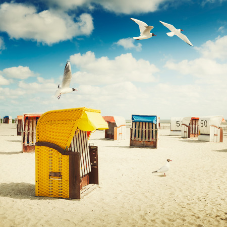 Hooded chairs on sand beach. Sea gulls flying in blue cloudy sky. Vacation background. North sea coast, travel destination. Toned in warm colors Standard-Bild