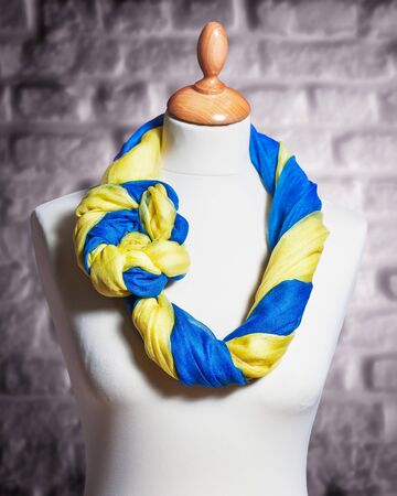 single object: Mannequin with silk cloth. Knitted fashion blue and yellow organza shawls on tailor bust. Single object with clipping path
