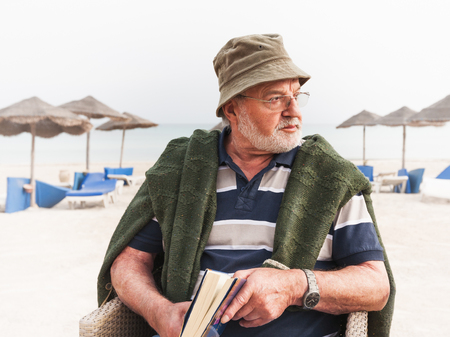 adult 80s: Senior man relaxing on tropical winter beach. Vacation resort Stock Photo